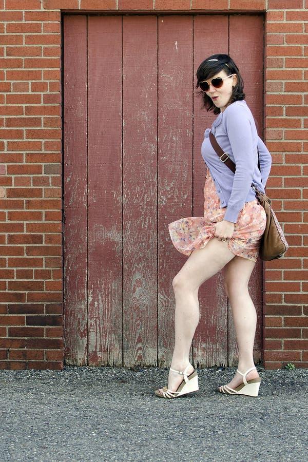 Ung kvinna som framme poserar av tegelstenväggen royaltyfria foton