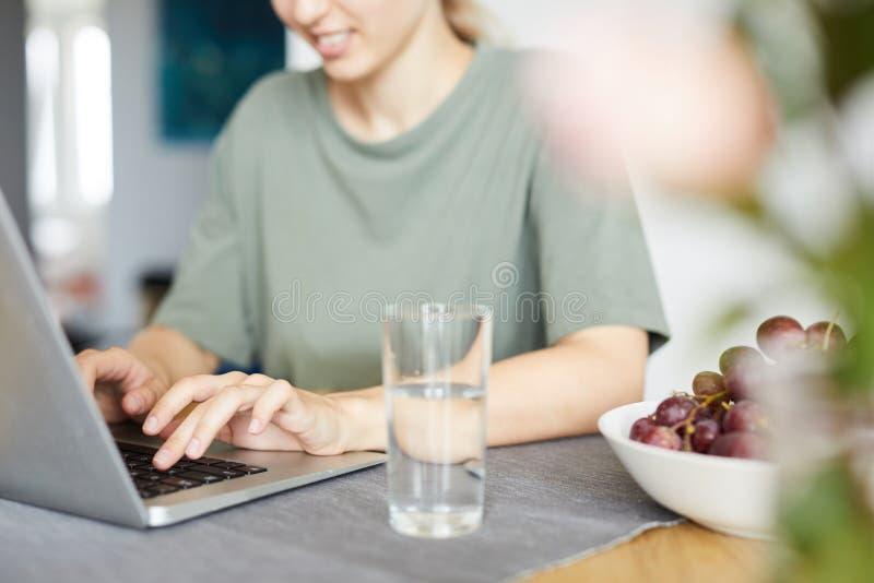 Ung kvinna som framme sitter av bärbara datorn vid köksbordet hemma fotografering för bildbyråer