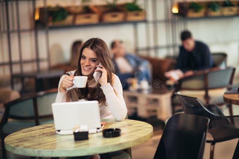 Ung kvinna som framme sitter av den öppna bärbar datordatoren i kaféstång arkivfoton