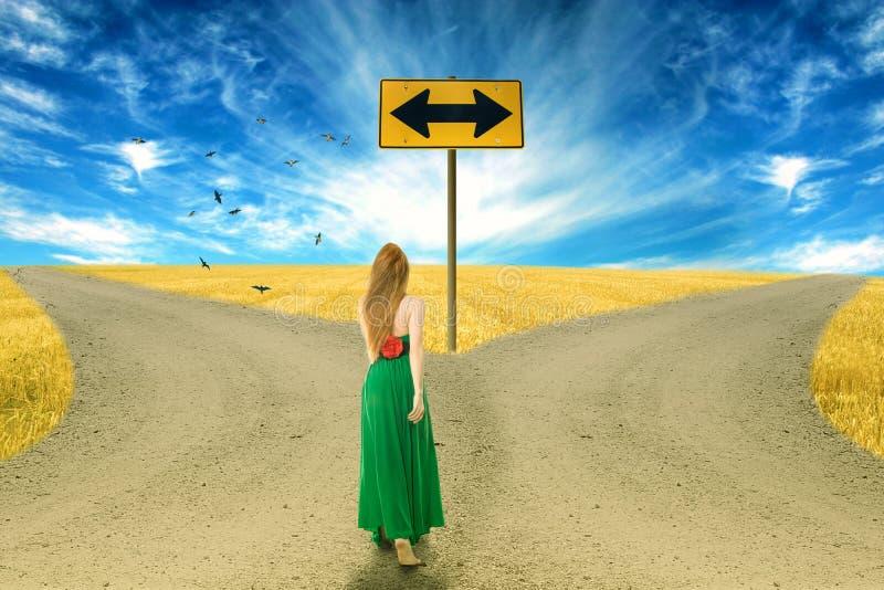Ung kvinna som framme står av två vägar arkivfoto