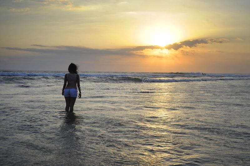 Ung kvinna som fridfullt mediterar och tänker på ökenstranden på solnedgång i meditation och frihet arkivfoton