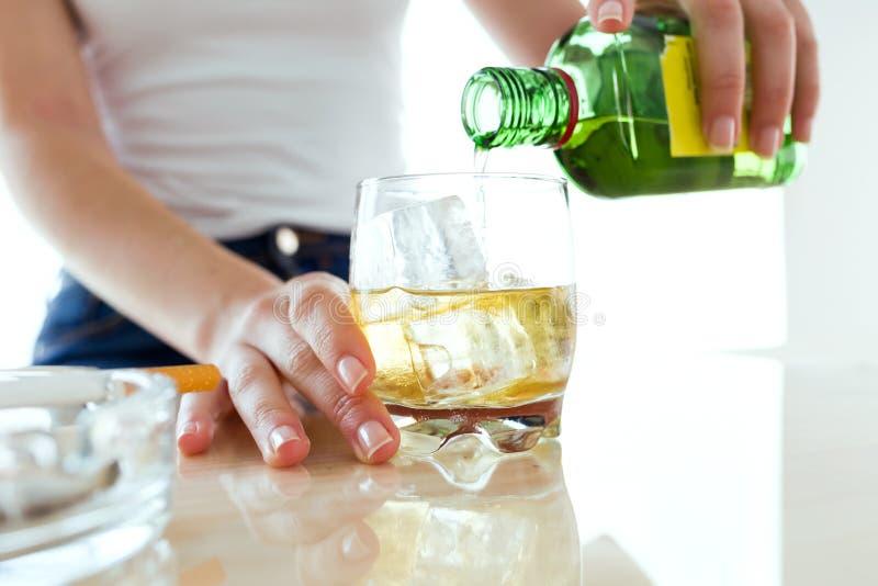 Ung kvinna som fyller ett exponeringsglas av whisky royaltyfri foto