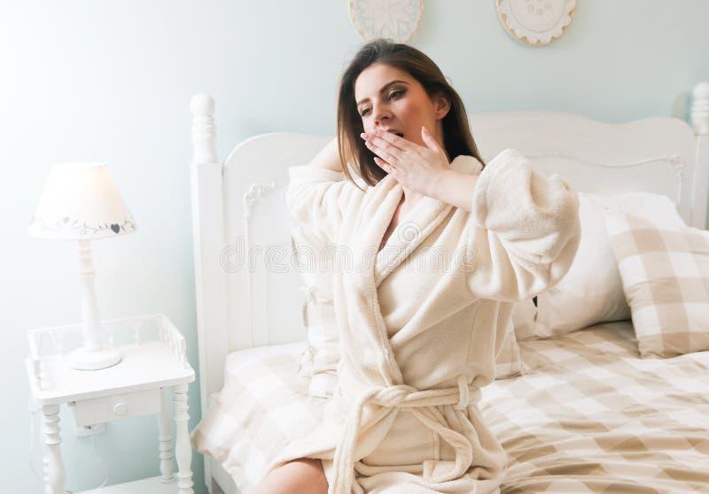 Ung kvinna som går att bädda ned - få ut ur sängen royaltyfri fotografi