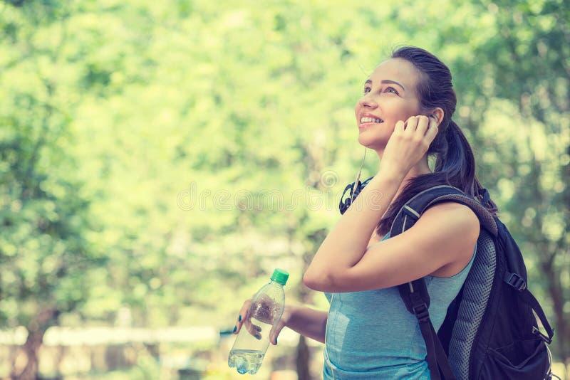 Ung kvinna som går att fotvandra i en skog arkivbild