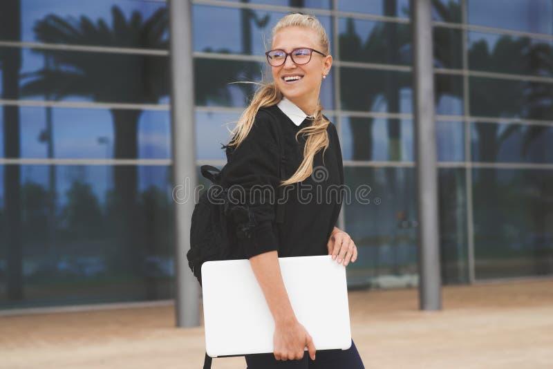 Ung kvinna som går av kontorsbyggnaden som rymmer en bärbar dator royaltyfri fotografi