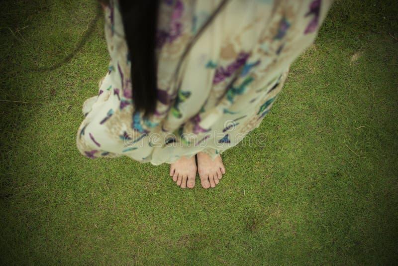 Ung kvinna som g?r barfota p? det nya gr?na gr?set i solig sommar i morgonen Vilsamt ?gonblick Sund livsstil Brigh fotografering för bildbyråer