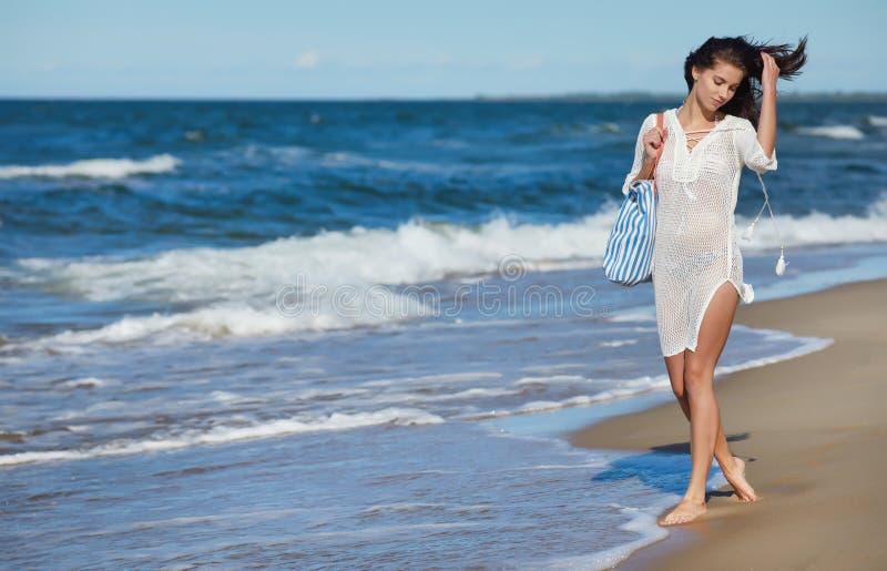 Ung kvinna som går i bärande vit strandklänning för vatten royaltyfri foto
