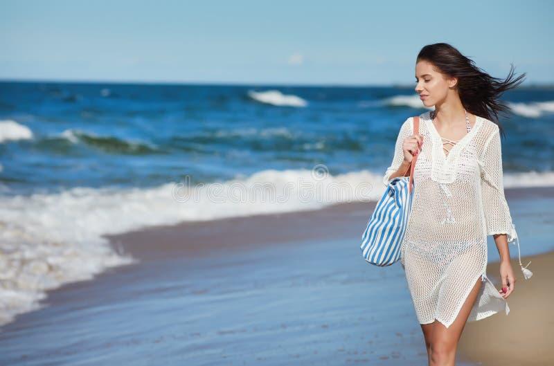 Ung kvinna som går i bärande vit strandklänning för vatten royaltyfria bilder