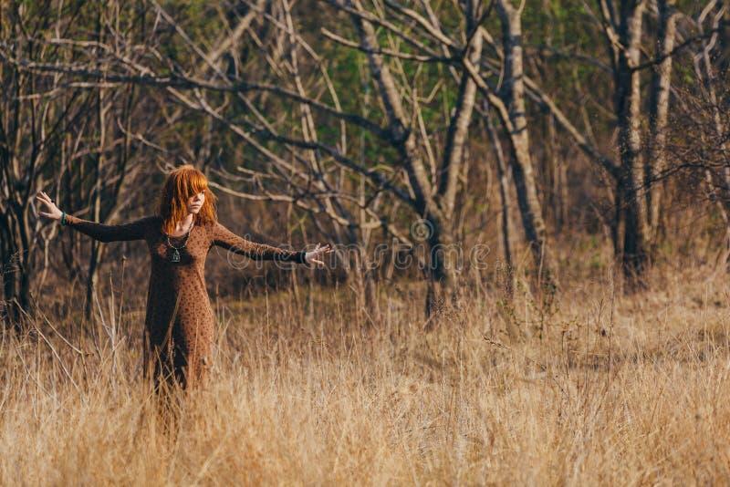 Ung kvinna som går i guld- fält för torkat gräs royaltyfri bild
