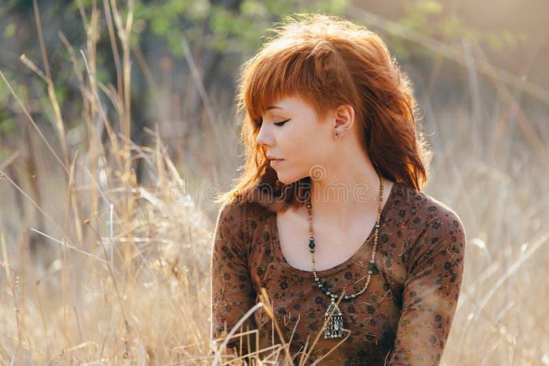 Ung kvinna som går i guld- fält för torkat gräs royaltyfria foton