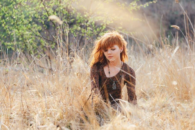 Ung kvinna som går i guld- fält för torkat gräs fotografering för bildbyråer