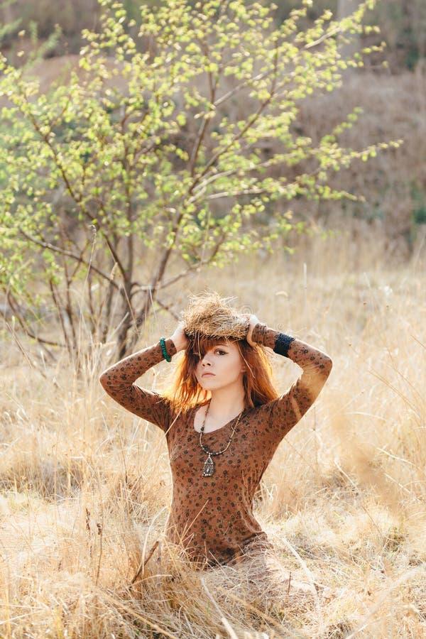 Ung kvinna som går i guld- fält för torkat gräs royaltyfri foto
