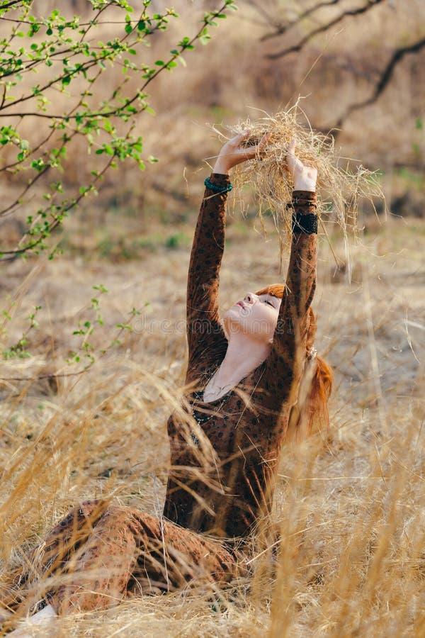 Ung kvinna som går i guld- fält för torkat gräs arkivbilder