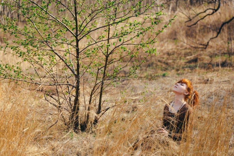 Ung kvinna som går i guld- fält för torkat gräs royaltyfria bilder