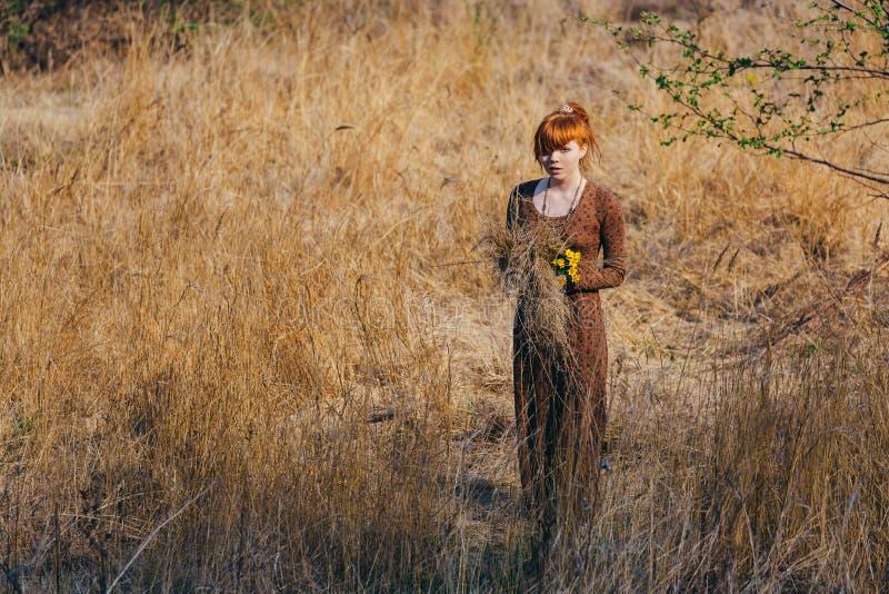 Ung kvinna som går i guld- fält för torkat gräs arkivbild