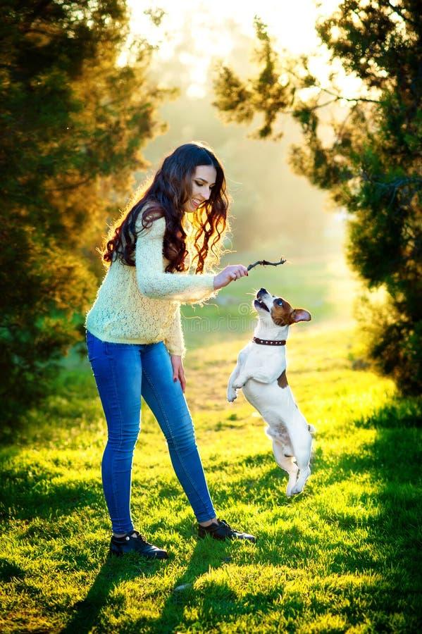 Ung kvinna som går med en hund som spelar utbildning, banhoppninghund stålarrussell terrier royaltyfri foto