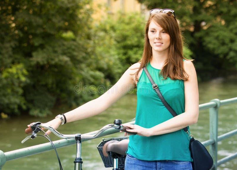 Ung kvinna som går med hennes cykel vid floden royaltyfri bild