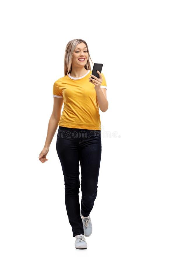 Ung kvinna som går och använder en telefon royaltyfri fotografi