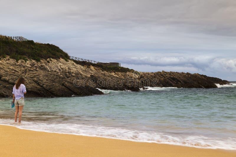 Ung kvinna som går på sanden av en härlig strand royaltyfri fotografi
