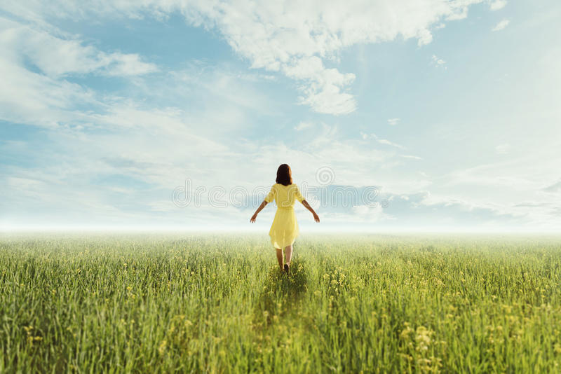 Ung kvinna som går på sommaräng royaltyfri fotografi