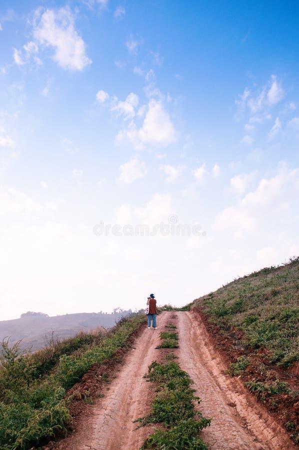 Ung kvinna som går på vägen för smutsbanaland på kullen på helgdagsaftonen arkivfoton