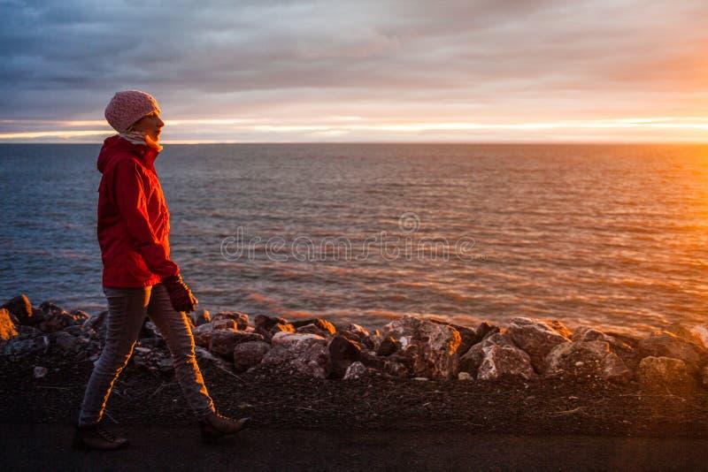 Ung kvinna som går under solnedgång på en kall afton arkivfoton