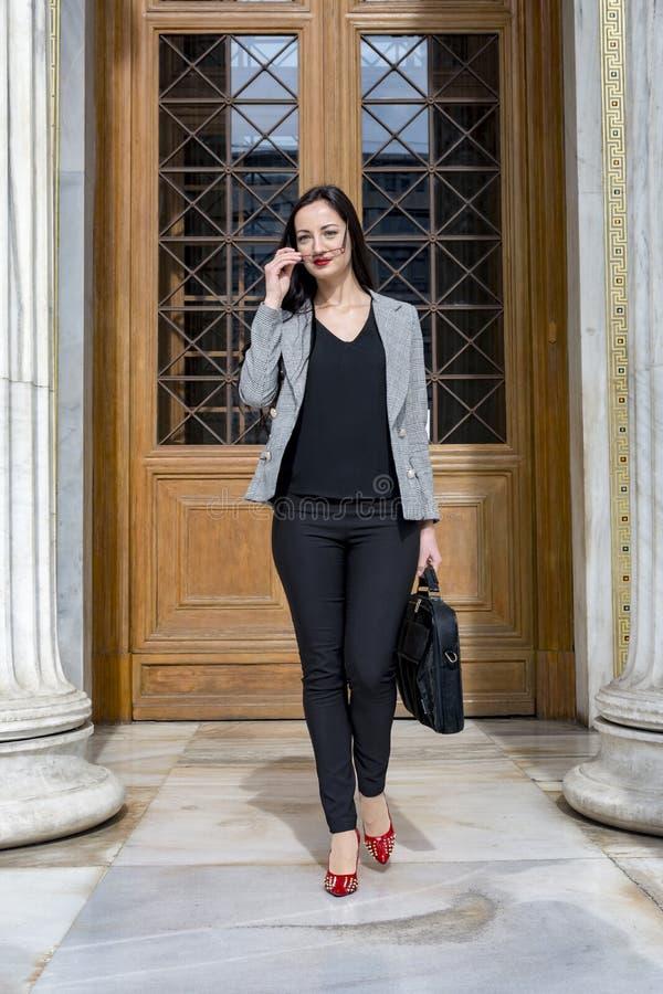 Ung kvinna som går ut från en byggnad fotografering för bildbyråer
