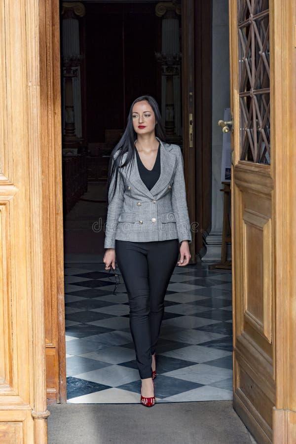 Ung kvinna som går ut från en dörr royaltyfri bild