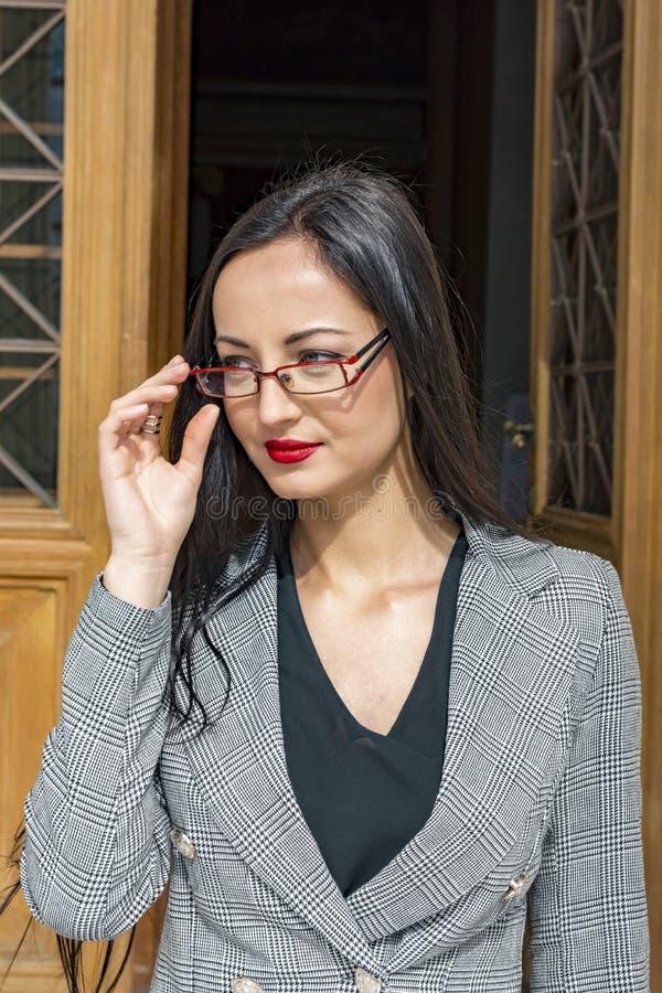 Ung kvinna som går ut från en dörr royaltyfri foto