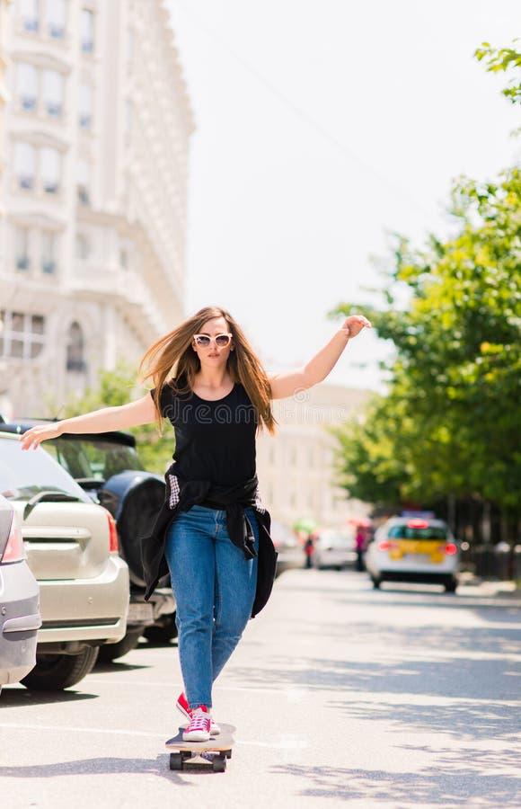Ung kvinna som gör som är sluttande med en skateboard royaltyfria foton