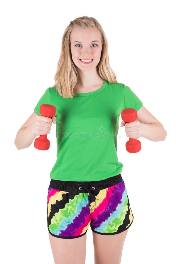 Ung kvinna som gör övning med röda hantlar i sportswear royaltyfria bilder