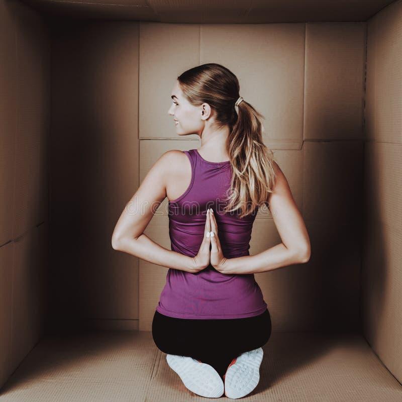 Ung kvinna som gör övningar i kartong arkivbilder