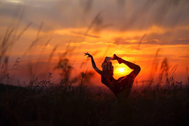 Ung kvinna som gör böjlig dansflyttning under solnedgång royaltyfri bild