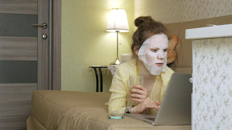 Ung kvinna som gör den ansikts- maskeringsmaskeringen med att rentvå maskeringen som hemma arbetar bak bärbara datorn arkivfoton