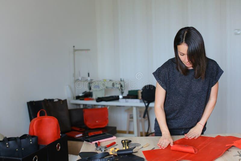 Ung kvinna som gör den röda läderplånboken på atelieren royaltyfria bilder