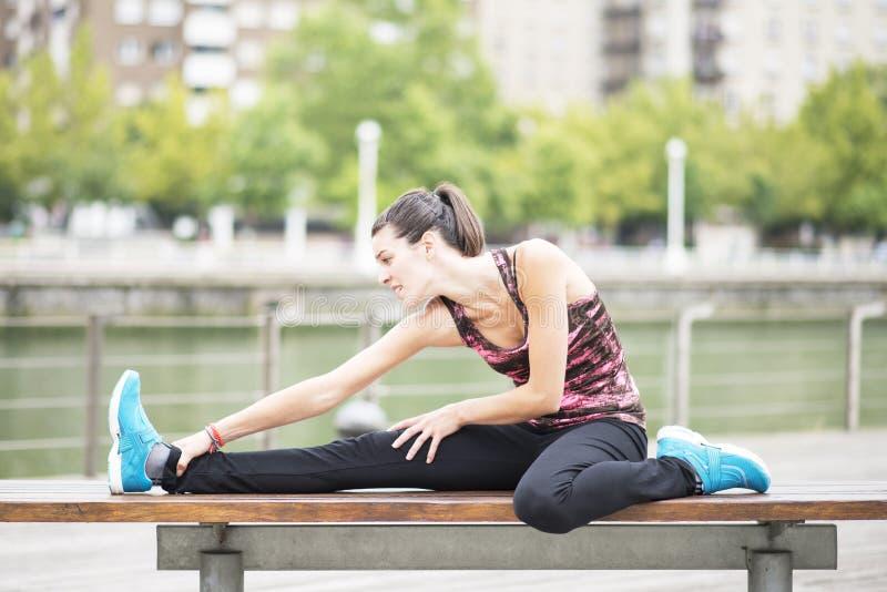 Ung kvinna som gör elasticiteter i staden. arkivfoto