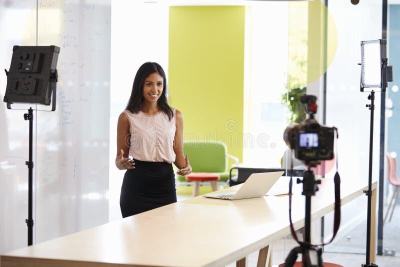 Ung kvinna som gör en företags demonstrationsvideo royaltyfri fotografi
