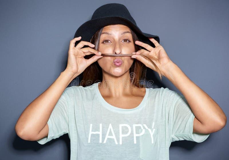 Ung kvinna som gör en mustasch med hennes hår arkivbild