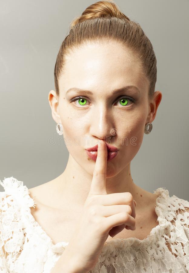 Ung kvinna som gör en tystnadgest royaltyfria foton