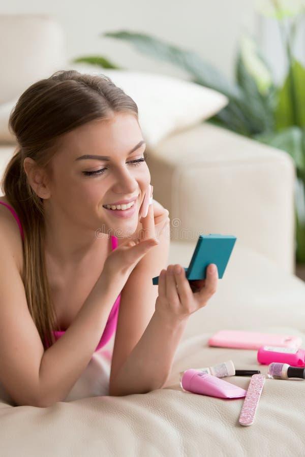 Ung kvinna som gör enkel daglig makeup hemmastadd royaltyfria foton