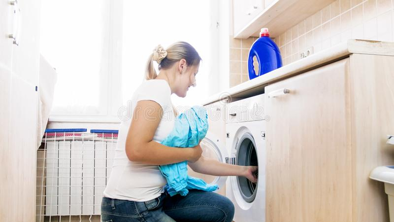 Ung kvinna som gör hushållsarbete i tvätteri arkivbilder