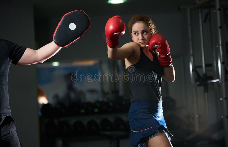 Ung kvinna som gör kickboxing utbildning med hennes lagledare arkivbilder
