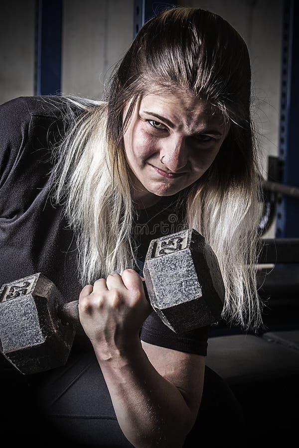 Ung kvinna som gör krullning med en hantel i Connecticut royaltyfri fotografi