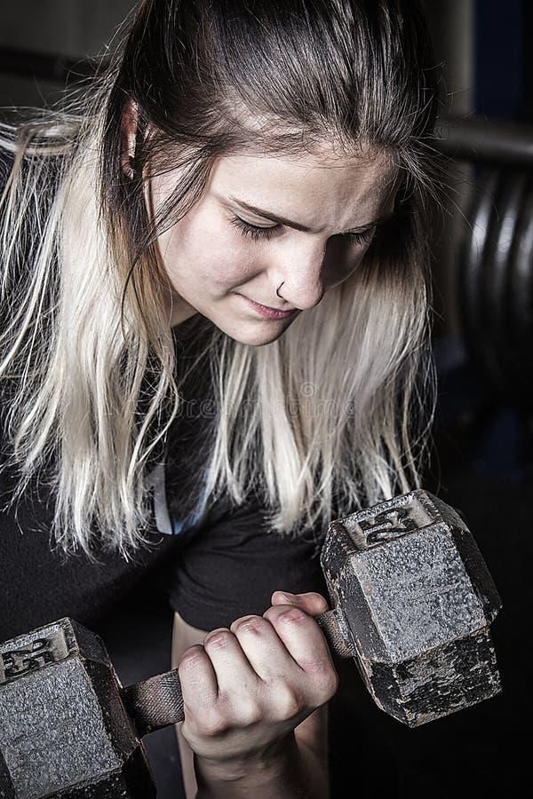 Ung kvinna som gör krullning med en hantel i Connecticut royaltyfri foto