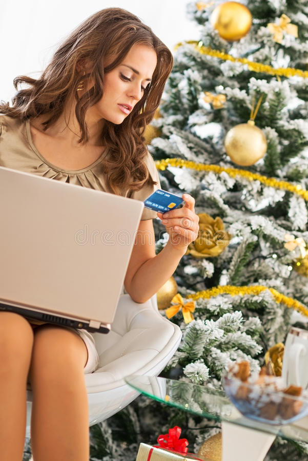 Ung kvinna som gör online-shopping nära julträd royaltyfri bild