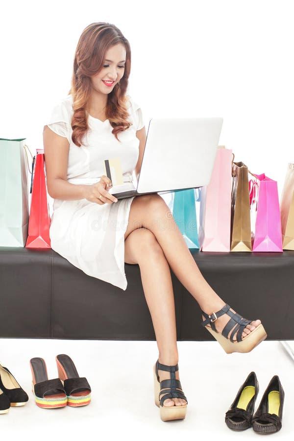 Ung kvinna som gör online-transaktion och sitter mellan shopping arkivfoton