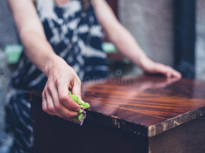 Ung kvinna som gör ren gammalt möblemang fotografering för bildbyråer