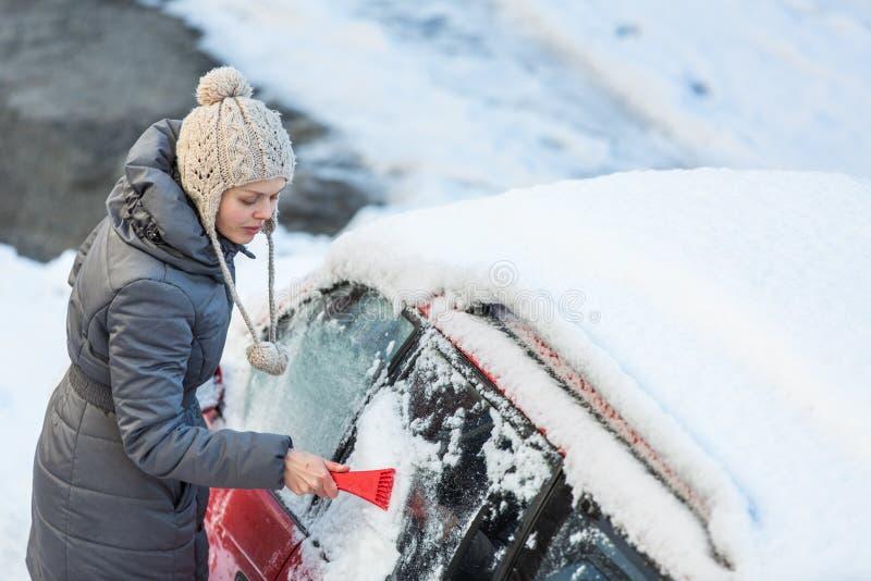 Ung kvinna som gör ren hennes bil från snö och frost royaltyfri foto