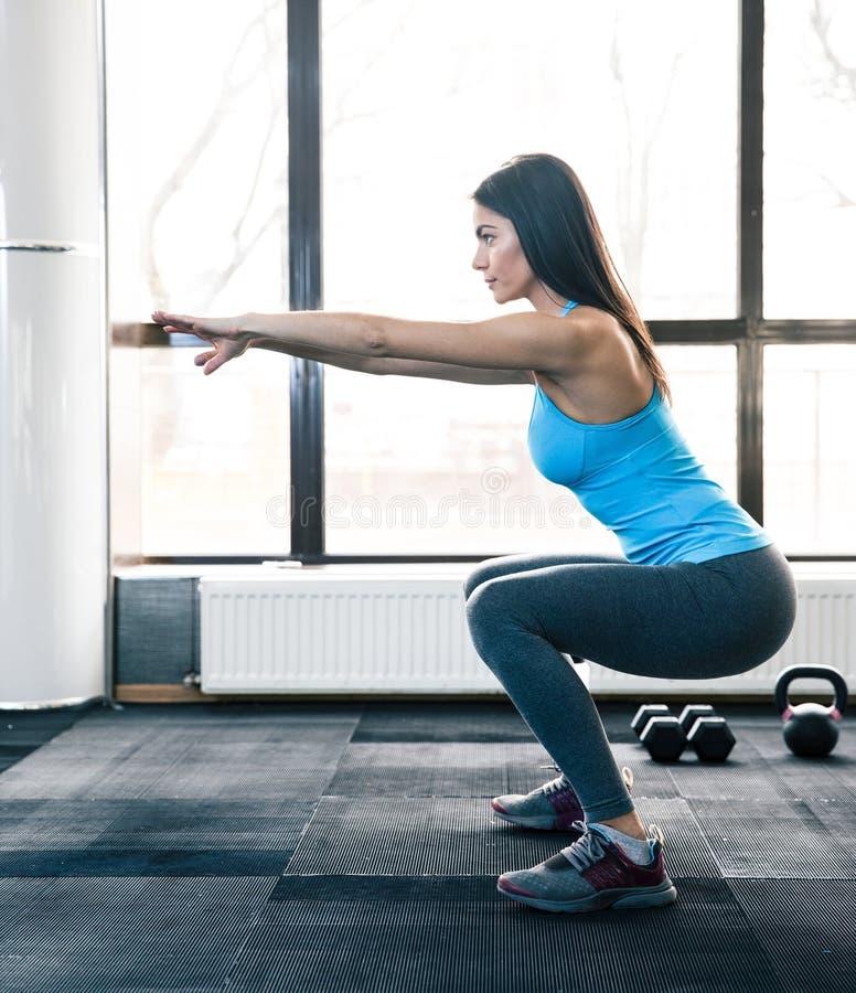 Ung kvinna som gör squats arkivfoton