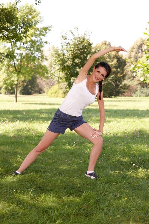 Ung kvinna som gör sträcka övning på gräs royaltyfri fotografi